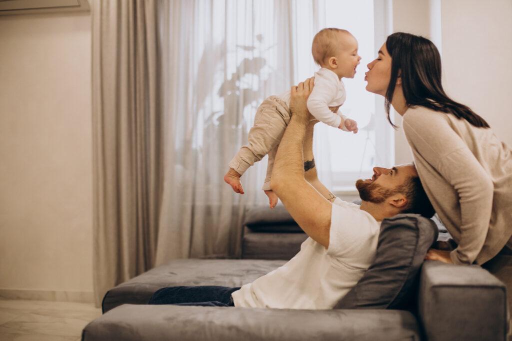 Zdjęcie trzyosobowej rodziny - mężczyzna, kobieta i niemowlak. Znajdują się w pokoju, mężczyzna siedzi na kanapie i trzymając dziecko w górze, podaje je kobiecie do pocałowania.
