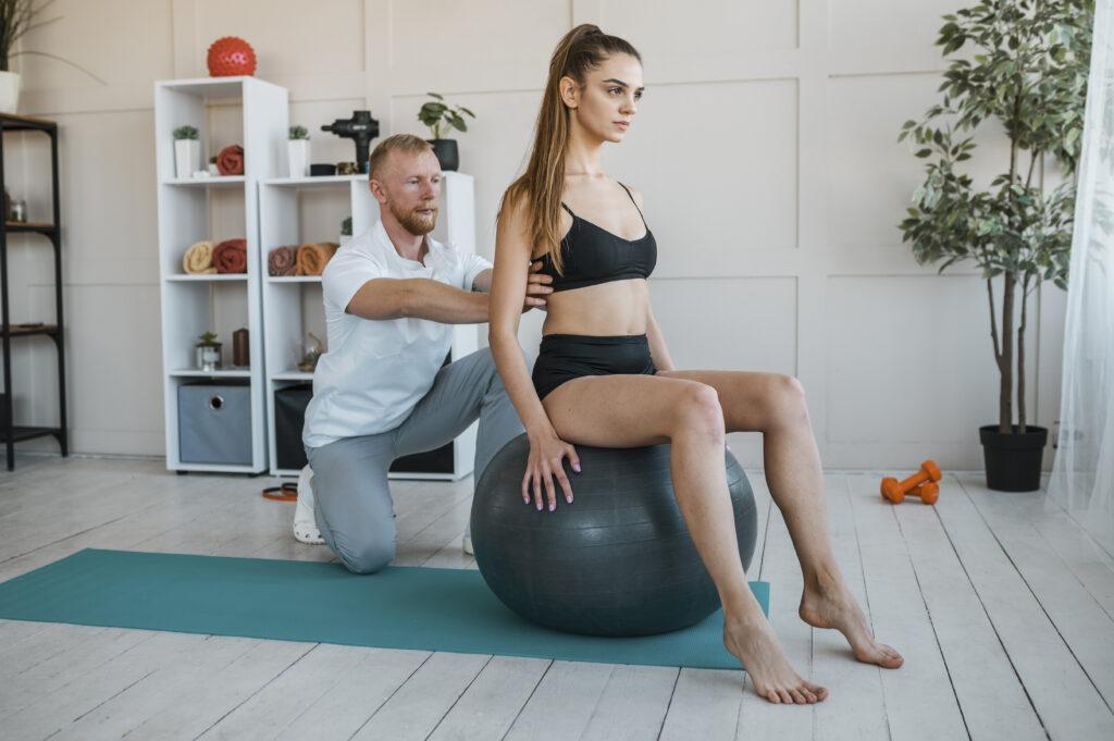 Fizjoterapeuta PNF pracuje na macie z pacjentem z piłką